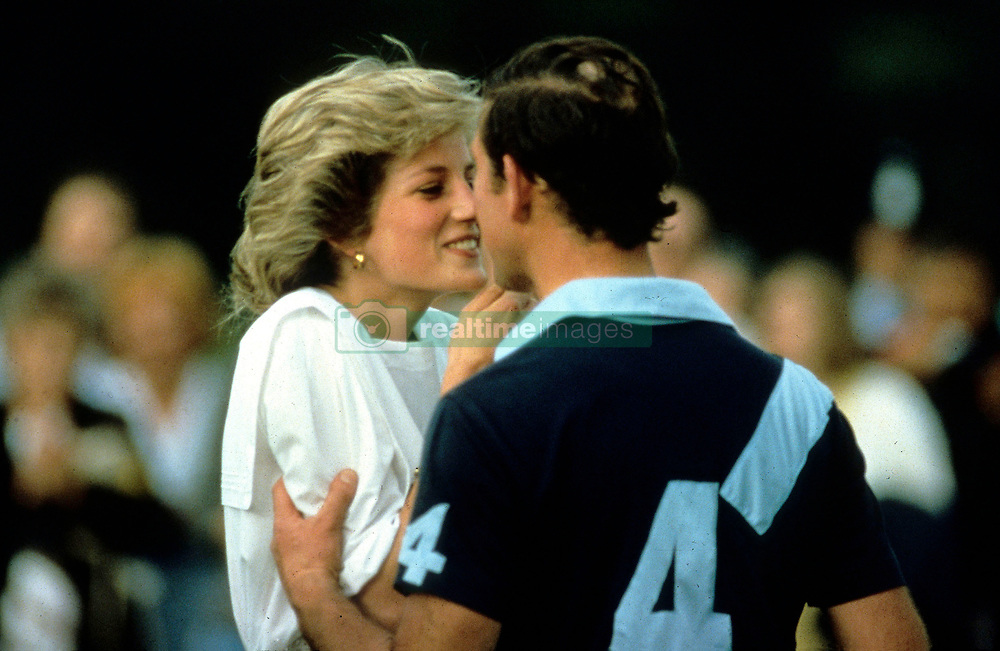 Diana, Princess of Wales and Prince Charles, Prince of Wales kiss during a polo match at Cirencester Polo Club in July, 1985.