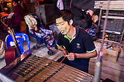 "25 JANUARY 2014 - BANG LUANG, NAKHON PATHOM, THAILAND: A musician with the Sing Tong Teochew opera troupe rehearses before a show in a Chinese shrine in the town of Bang Luang, Nakhon Pathom, Thailand. The Sing Tong Teochew opera troupe has been together for 60 years and travels through central Thailand and Bangkok performing for mostly ethnic Chinese audiences. Chinese opera was once very popular in Thailand, where it is called ""Ngiew."" It is usually performed in the Teochew language. Millions of Chinese emigrated to Thailand (then Siam) in the 18th and 19th centuries and brought their cultural practices with them. Recently the popularity of ngiew has faded as people turn to performances of opera on DVD or movies. There are still as many 30 Chinese opera troupes left in Bangkok and its environs. They are especially busy during Chinese New Year when travel from Chinese temple to Chinese temple performing on stages they put up in streets near the temple, sometimes sleeping on hammocks they sling under their stage.     PHOTO BY JACK KURTZ"