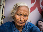 02 AUGUST 2015 - BHAKTAPUR, NEPAL:  An elderly woman in a small Internal Displaced Person (IDP) camp at Durbar Square in Bhaktapur for people left homeless by the Nepal earthquake. The Nepal Earthquake on April 25, 2015, (also known as the Gorkha earthquake) killed more than 9,000 people and injured more than 23,000. It had a magnitude of 7.8. The epicenter was east of the district of Lamjung, and its hypocenter was at a depth of approximately 15 km (9.3 mi). It was the worst natural disaster to strike Nepal since the 1934 Nepal–Bihar earthquake. The earthquake triggered an avalanche on Mount Everest, killing at least 19. The earthquake also set off an avalanche in the Langtang valley, where 250 people were reported missing. Hundreds of thousands of people were made homeless with entire villages flattened across many districts of the country. Centuries-old buildings were destroyed at UNESCO World Heritage sites in the Kathmandu Valley, including some at the Kathmandu Durbar Square, the Patan Durbar Squar, the Bhaktapur Durbar Square, the Changu Narayan Temple and the Swayambhunath Stupa. Geophysicists and other experts had warned for decades that Nepal was vulnerable to a deadly earthquake, particularly because of its geology, urbanization, and architecture.      PHOTO BY JACK KURTZ