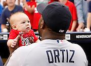 Boston Red Sox' David Ortiz holds a fan's baby before their baseball game against the Kansas City Royals at Kauffman Stadium in Kansas City, Mo., Thursday, Aug. 8, 2013. (AP Photo/Colin E. Braley)