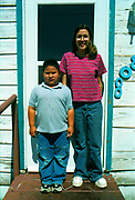 American boy and girl standing on the front step in-front of their house, USA, 2000's