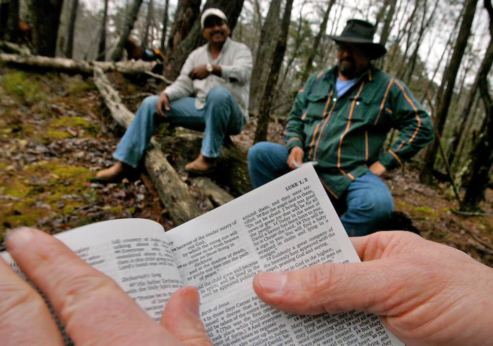 """Passages from the Bible are read to David Velazquez, left, and Mike Burkett, right, during a Cowboy Church saddle-back Bible study on Morrow Mountain. The Bible study brings another fellowship opportunity to members of the Cowboy Church. """"It's brought me closer to Jesus,"""" Burkett said."""