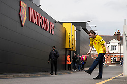 A Watford fan plays football outside Vicarage Road prior to the match