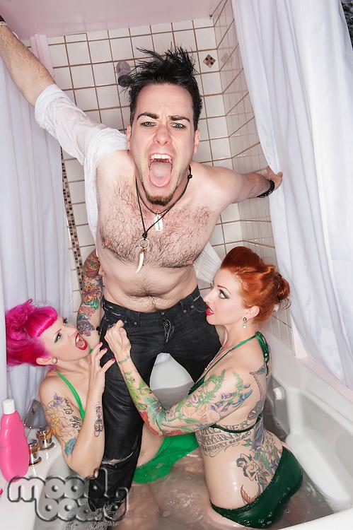 Funky women seducing man in a bathtub