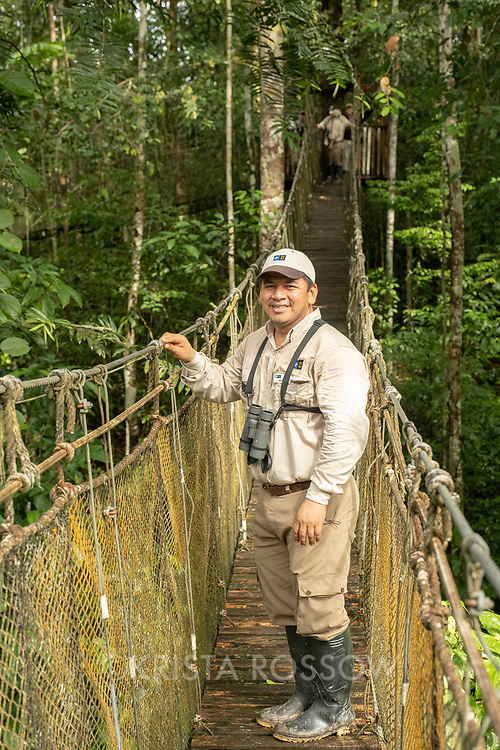 Naturalist Jairo Flores on the canopy walk in the tropical rainforest at Amazon Natural Park.