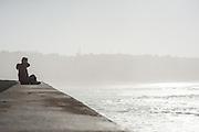 Woman sat on balaustrade overlooking the sea in San Sebastian (Spain)