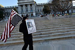 Mike Gasm, of Middletown, PA, marches with a flag at the steps of  the State Capitol steps in anticipation of members of the Electoral College, in Harrisburg, PA, on Dec. 19th, 2016