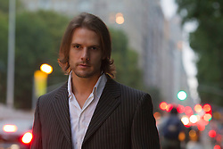 man with long hair wearing a blazer and open shirt on the street in New York City