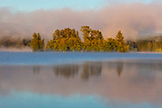 Fog rises off Alder Lake and is turned red by the rising sun near Eatonville, Washington. Alder Lake is a reservoir created by a dam on the Nisqually River.