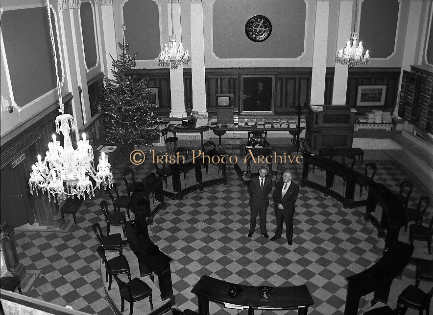 """Mr Angus McDonnell (left), President of the Stock Exchange and Mr Owen Kealy, Managing Director, Waterford Glass Group, on the Stock Exchange trading floor to view the chandeliers from below.<br /> <br /> Waterford Glass Chandeliers in the Stock Exchange 18th December 1985..The installation of four Water Crystal Chandeliers over the trading floor in the Stock Exchange added an air of elegance to the room. It was regarded by many as the """"Highlight"""" of this Christmas period."""