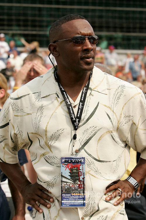 Former college and pro football star Tim Brown watches the action during qualifications for the Allstate 400 at the Brickyard.