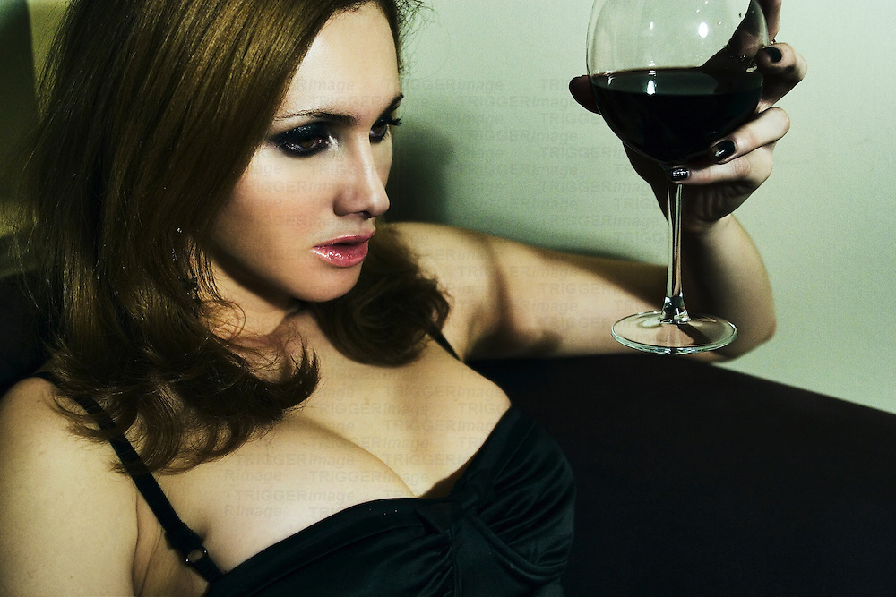 A young woman holding a glass of red wine