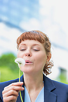 Portrait of young attractive businesswoman wishing on dandelion