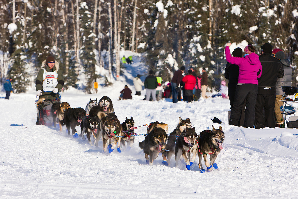 Musher Michael Williams Jr. competing in the 40th Iditarod Trail Sled Dog Race on Long Lake after leaving the Willow Lake area at the restart in Southcentral Alaska. Afternoon. Winter.