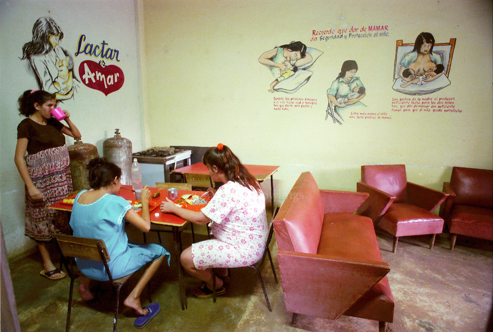 Women eat lunch under murals promoting breast feeding in a home for expectant mothers in Viñales, Cuba. Since transportation is difficult to come by in the countryside, women can stay in a home where they receive nursing care while sick or close to their due date.