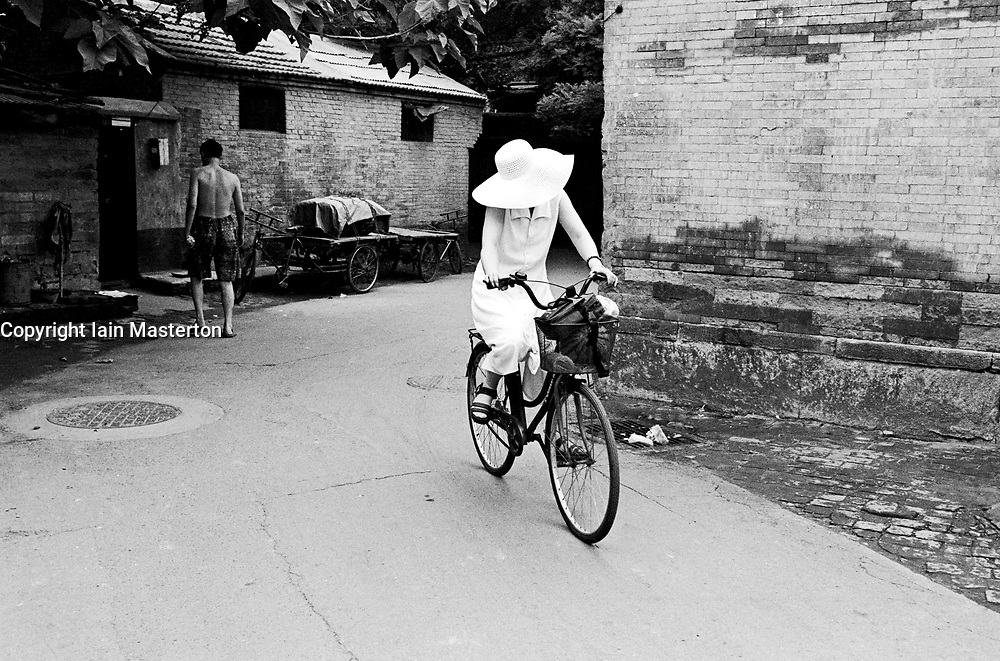 Woman in summer dress cycling through hutong in Beijing China