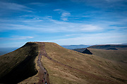 People walking across the summit of Corn Du twin topped with Pen y Fan and is the second highest peak in South Wales in the Brecon Beacons National Park, United Kingdom.  The rugged path connects the two mountain peaks.  The National Park was established in 1957 due to the spectacular landscape which is rich in natural beauty and is run by the National Trust.  (photo by Andrew Aitchison / In pictures via Getty Images)