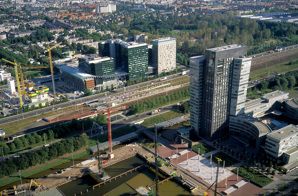Nederland, Amsterdam, Zuidas, Mahlerlaan, 25-09-2002; hoofdkantoor van de ABN AMRO bank met bouwplaats aanstaande uitbreiding (linksonder); midden ringweg A10 met NS en metro station Zuid-WTC, daarachter het World Trade Centre (WTC) met nieuwe toren (rechts) en bouwplaats verdere uitbreiding (links).bouwen, bouwkraan, bank, verzekeringen, economie, handel, bedrijvigheid, stadsgezicht; zie ook andere foto's van deze lokatie;<br /> luchtfoto (toeslag), aerial photo (additional fee)<br /> foto /photo Siebe Swart