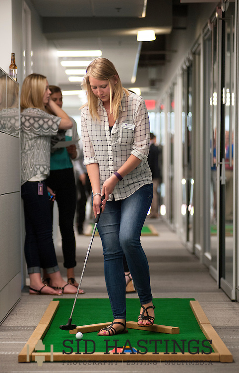 2 JUNE 2016 -- ST. LOUIS -- Lindsay Beauchamp of Anders CPAs + Advisors prepares to putt on the putt-putt course laid out among the offices at the company in downtown St. Louis as part of Putt and Prosper 2016 Thursday, June 2, 2016. An after work happy hour sponsored by Anders' Young Professional Group for employees, customers and friends, Putt and Prosper scattered putt-putt holes throughout the firm's offices and raised funds for Stray Rescue of St. Louis. Photo © copyright 2016 Sid Hastings.
