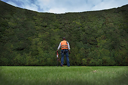 © Licensed to London News Pictures. 07/08/2017. Cirencester, UK. Forester Jason Buckton looks up at the world's tallest yew hedge on The Bathurst Estate during cutting.  The 40 foot tall 150 yard wide hedge is trimmed every august over a two week period. Six inches of growth are cut making a ton of clippings. The clippings have been used in past years in the making of a cancer drug.   Photo credit: Peter Macdiarmid/LNP