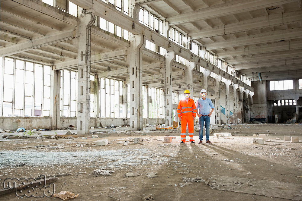 Full length of construction workers in protective workwear at site