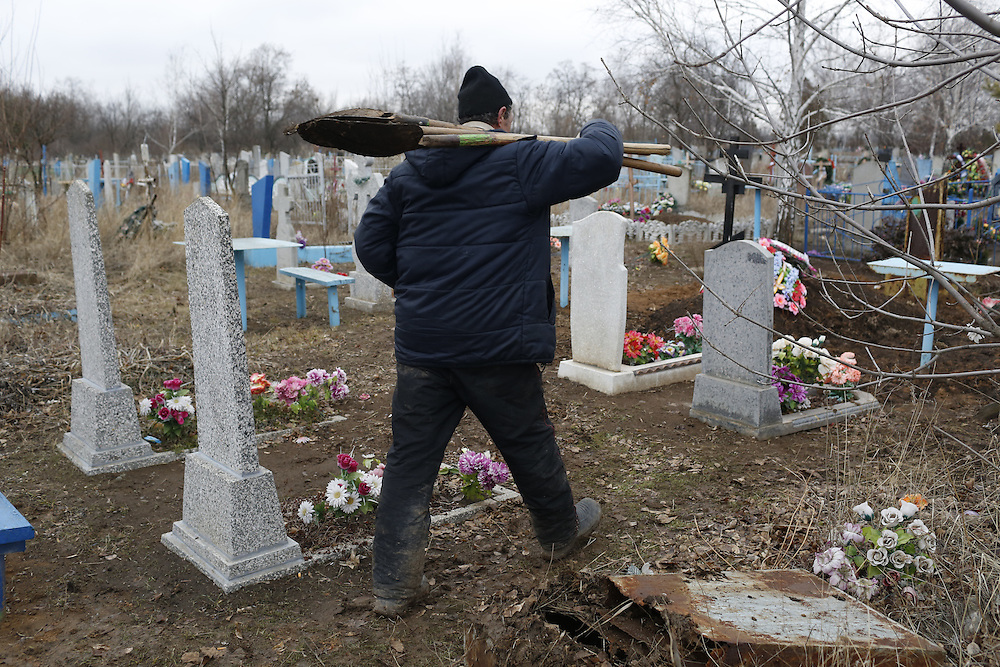 Gravedigger Yura Pukhovets walks through a graveyard on February 6, 2015 in Luhanske, Donetsk Oblast, Ukraine. The cemetery was struck twice in recent days by shelling, and Pukhovets says they have been digging 2-3 graves per day on account of the conflict.