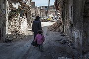 Sawsan, 42, and her daughter walk towards their home in the old quarter of Mosul, which they returned to in February 2018. <br />