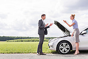 Full length side view of business couple arguing over broken car at countryside