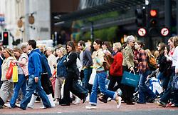 Pedestrians crossing street in central Glasgow Scotland
