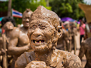 28 JUNE 2014 - DAN SAI, LOEI, THAILAND: A man covered in mud from the Mun River during the Ghost Festival parade in Dan Sai. Phi Ta Khon (also spelled Pee Ta Khon) is the Ghost Festival. Over three days, the town's residents invite protection from Phra U-pakut, the spirit that lives in the Mun River, which runs through Dan Sai. People in the town and surrounding villages wear costumes made of patchwork and ornate masks and are thought be ghosts who were awoken from the dead when Vessantra Jataka (one of the Buddhas) came out of the forest.    PHOTO BY JACK KURTZ