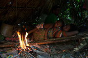 A child feeds from his mother inside their traditional shelter.<br /> <br /> Evidence suggests that the Maniq, a Negrito tribe of hunters and gatherers, have inhabited the Malay Peninsula for around 25,000 years. Today a population of approximately 350 maniq remain, marooned on a forest covered mountain range in Southern Thailand. Whilst some have left their traditional life forming small villages, the majority still live the way they have for millennia, moving around the forest following food sources. <br /> <br /> Quiet and reclusive they are little known even in Thailand itself but due to rapid deforestation they are finding it harder to survive on the forest alone and are slowly being forced to move to its peripheries closer to Thai communities.
