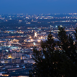 Background of shining lights of the city with illumination and traffic. The silhouette of a plant blown by the wind on the foreground. Blue tone. Shot in Bergamo, Italy