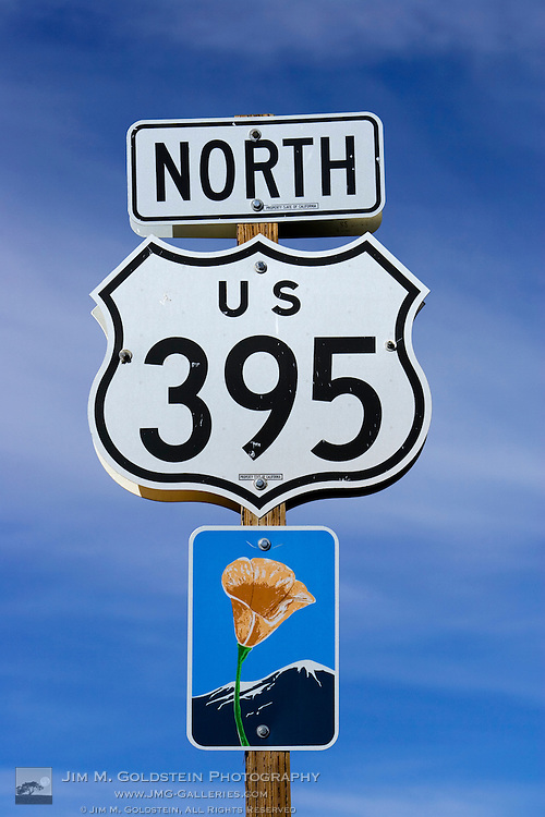 An upward view of a Highway 395 North sign post including a California Scenic Highway sign.