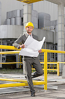 Full length portrait of young male architect with blueprint outside industry