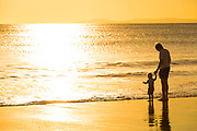 Father and Son Standing Along the Shore at Sunset in Laguna Beach
