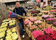 © Licensed to London News Pictures. 15/03/2012. London, UK. Charlie Hickson sorts out bunches of flowers on the stall he works on. The Mothering Sunday sales rush is on for flower growers, suppliers, florists and retailers amongst the Flowers at the New Covent Garden Flower Market on March 15th 2012 in London, England. New Covent Garden Flower Market is London's premier wholesale market stocking the widest range of flowers, plants and foliage in the UK. The run up to Mothers' Day is crucial in the flower selling calendar as Mothers' Day sales are condensed into about four days making the market very busy. Traditionally, Mothering Sunday was a day when children, mainly daughters, who had gone to work as domestic servants, were given a day off to visit their mother and family. Today, Mother's Day is a time when children give flowers and cards to their mothers, and generally pamper them..  Photo credit : Stephen SImpson/LNP