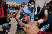 A wounded Libyan opposition rebel is carried from the Ras Lanouf hospital March 06, 2011 in Ras Lanouf, Libya. The fighter was wounded as he and other rebels fought pro-Qaddafi forces in the nearby town of Bin Jaweed, a day after that city fell to government forces.