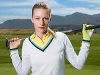 Young female golfer holding club portrait