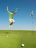 Young male golfer jumping on green