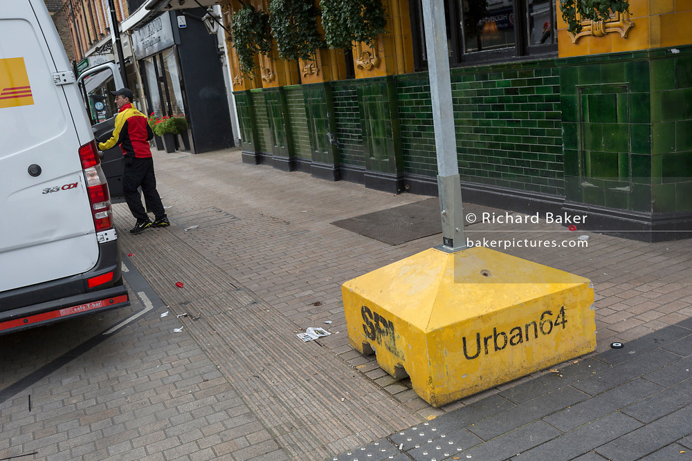 Parked outside a green and yellow-tiled Victorian pub, a DHL courier delivers packages in Bromley town centre, on 3rd February 2020, in Bromley, London, England.
