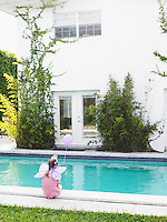 Young girl (7-9) in fairy wings sitting by swimming pool back view