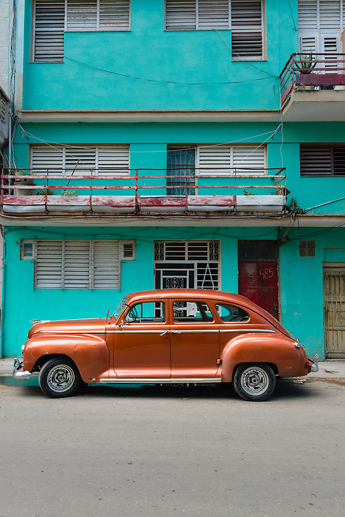 Vintage American car in front of a colourful building in Havana, Cuba