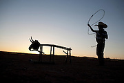 A young Navajo boy practices roping with his lasso or rope on a practice bull at sunset on the Navajo reservation in Chinle, Arizona