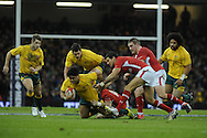 Australia's Ben Tapuai is tackled by Rhys Priestland and Mike Phillips .Dove Men, autumn international test, Wales v Australia at the Millennium Stadium in Cardiff on Sat 1st Dec 2012. pic by Andrew Orchard, Andrew Orchard sports photography,