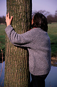 A912RF Woman hugging a tree