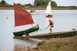 A man launching a Heybridge Roach dinghy on the Blackwater River in Essex.