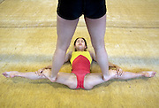 A girl helps her friend to stretch her legas during an afternoon training session of the Beijing Gymnastic team.