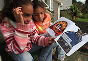 "From left, sisters Kamehana, 11 and Nahe Tachera, 9, whose great-grandfather, grandfather and father are or were all cowboys, look through Kamehana's scrapbook of cowboys pictures outside their home on Kahua Ranch in North Kohala, Hawaii.  The girls live with their father, Wayne Tachera, in ""cowboy housing"" on the ranch.  The girls learned to ride horses as toddlers and have grown up with the ranch as their playground. ""We're definitely cowgirls"", says Kamehana who regularly competes in rodeos."