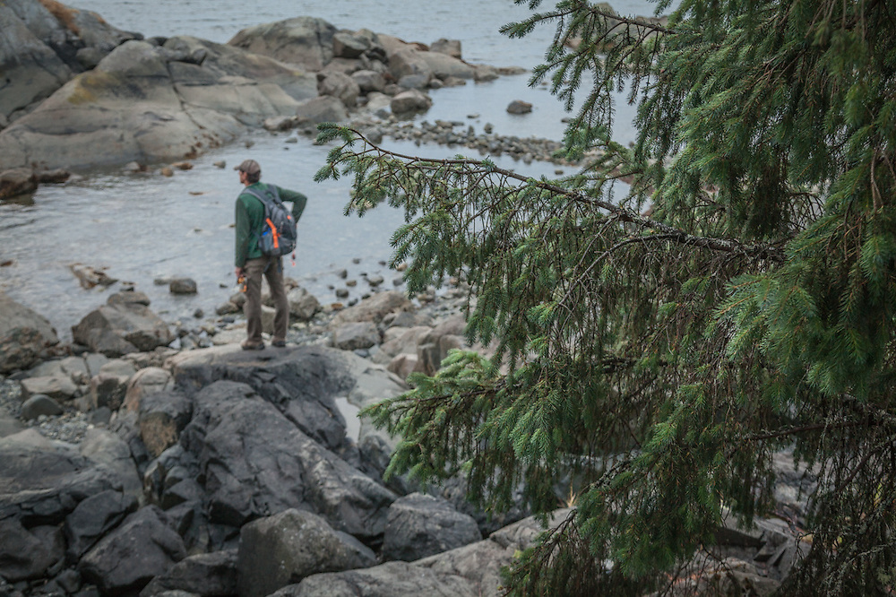 Troy assesses fish prospects at the edge of the sea in Sitka, Alaska