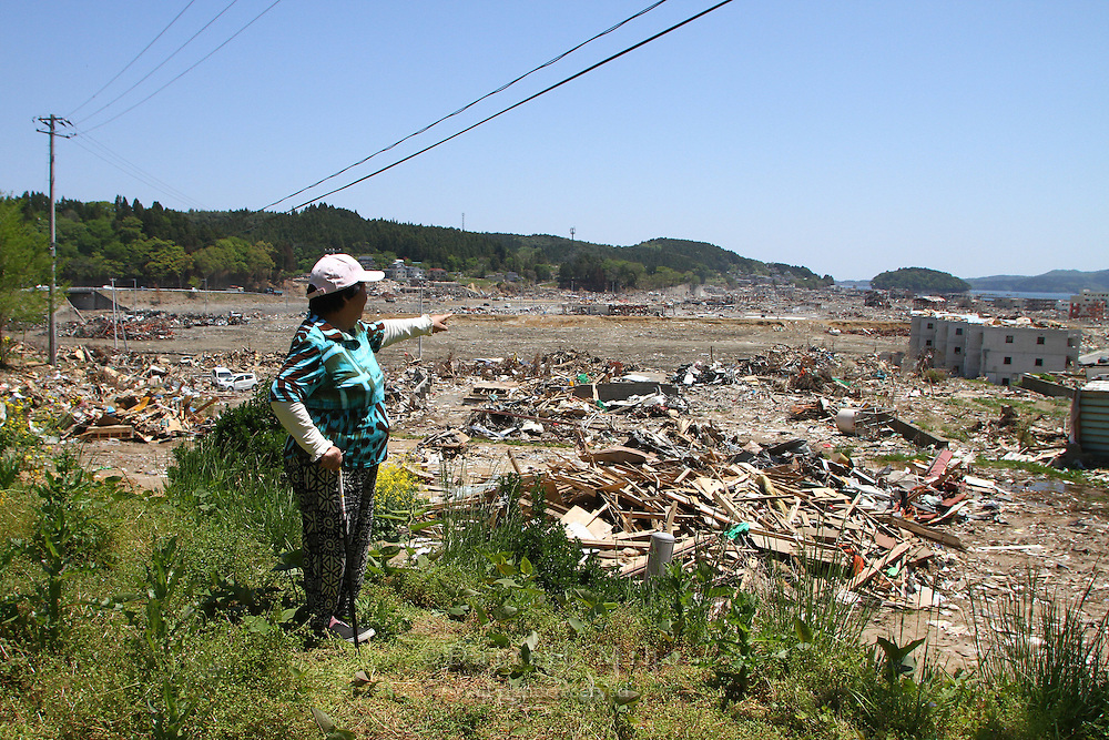 May 18, 2011; Minamisanriku, Miyagi Pref., Japan - From a hill overlooking the town of Minamisanriku, Kuniko Suzuki stands near the area where a fireman plucked her off the roof of a house that was floating in the tsunami floodwaters. She points to where her house used to be. ..This photo was taken over two months after the magnitude 9.0 Great Tohoku Earthquake and Tsunami devastated the Northeast coast of Japan on March 11, 2011.